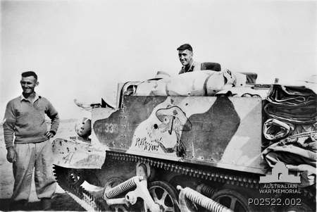 "VX47906 Corporal Frank Joseph Littlejohn (left) and another member of 2/32nd Battalion with a painted bren gun carrier. On the side is a painting of a rat holding a cigarette and the words ""rats to you"", symbolising the rats of Tobruk, painted by TX12 Private R. E. (Rufus) Webster. North Africa: Western Desert, Western Desert (Egypt), El Alamein. 1941."
