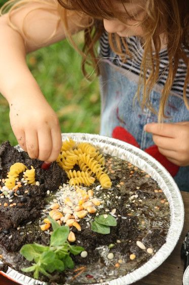 Can't wait to set this up for my kids. Mud kitchen: decorating a mud pie with dried pasta and lentils