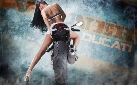 Девушка брюнетка с татуировкой дракона на спине сидит на спортивном мотоцикле.