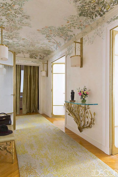 This hallway created by Persian designer Bridgette Saby makes a bold statement with it's hand painted #crown that draws your focus upward to the ceiling with the intertwined fruit branches that carry over the white crown. This is perfectly contrasted by the simple white baseboard and casing lining the perimeter of the room. #inspiration #crownmoulding #bridgettesaby #interiordecor #interiorfinishings #moulding