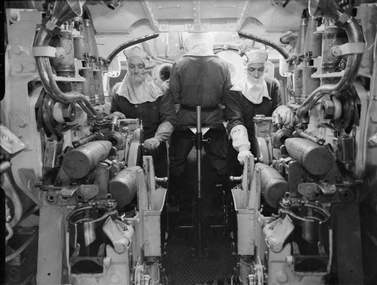 Inside a 5.25-inch gun turret on HMS King George V in 1943. The turret captain has his back to the camera as he observes the target through a periscope. The fuze setting machine operators are facing the camera, as they prepare to set the mechanical clock-work fuze in the two upper horizontal shells. As each shell's fuze is set the loaders (not shown) will remove it from the fuze setter and place it into the loading trays; the lower horizontal shells will then be automatically lifted into…