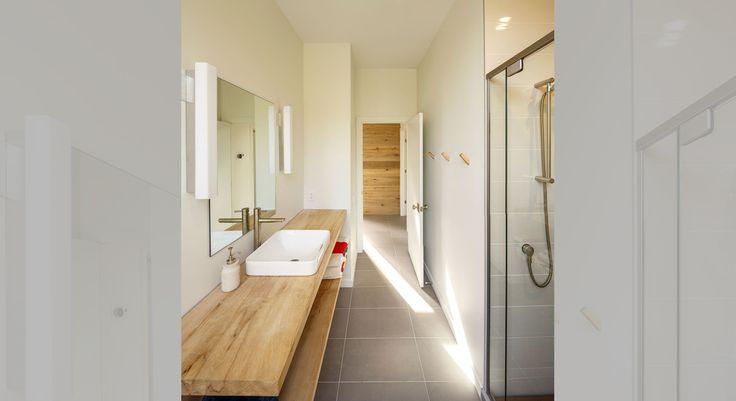 Деревянная столешница добавляет тепла в холодный интерьер ванной комнаты.  (современный,архитектура,дизайн,экстерьер,интерьер,дизайн интерьера,мебель,маленький дом,ванна,санузел,душ,туалет,дизайн ванной,интерьер ванной,сантехника,кафель) .