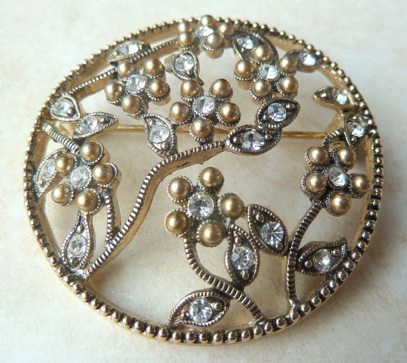 A vintage rhinestone detailed floral brooch by Monet.  The brooch is designed in a circular shape within which is an artfully arranged floral display of seven flowers, with surrounding leaves.  Each flower has a clear rhinestone center, as well as rhinestone detailing to the leaves.  Formed from textured silver tone metal, with a secure roll over safety fastening and is signed Monet to the back. Circa 1950's.