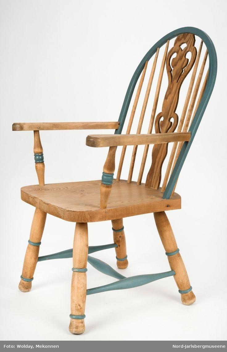 """""""Budal""""inspirert stol, med ryggstø og armelner. Ryggstø er formet av en blåmalt buet list som holdes oppe av seks vertikale trespiler. Den midter, og syvende, spilen er en bred, utskjært list med gjennombrutt mønster, stiliserte hjertemønster. Armlenene er buet utover, og ben og detaljer har dreid dekor."""