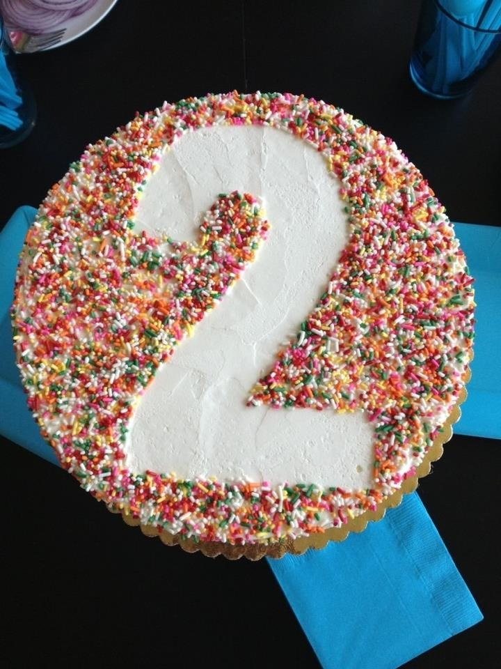 Place a baking paper template of any number or letter of your choice in the middle of a round iced cake, cover the rest of the cake with sprinkles and then remove the template! So easy! :)