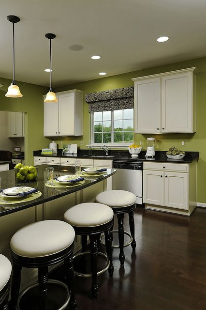 I love this kitchen!!!...green walls, white cabinets, black countertops and dark wood floor