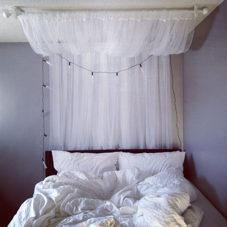 "DIY canopy: 2 curtain rods and 2 sets of LILL sheer curtains, (all from ikea). Mount one rod on the ceiling, and the other on the wall. ""Swoop"" to your liking. I finished it off with lights (also from Ikea), and a fluffy Ralph Lauren duvet, (thanks mom)."