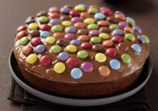 Préchauffez votre four Th.6 (200°C). A l'aide d'un grand couteau hachez le chocolat noir en pépites. Dans un saladier mélangez le yaourt, l'huile, les oeufs le sucre la farine et la levure. Ajoutez les pépites de chocolat. Versez dans un moule à manqué beurré et fariné et faites cuire 20 minutes. Démoulez et recouvrez de chocolat au lait fondu selon le mode d'emploi. Décorez de smarties. Placez au réfrigérateur environ 30 minutes.