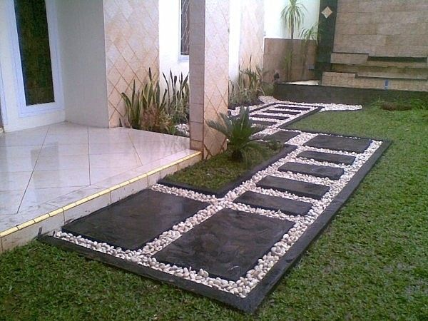 Create a path with black slate flagstones and snow white pebbles. Via Decoist.
