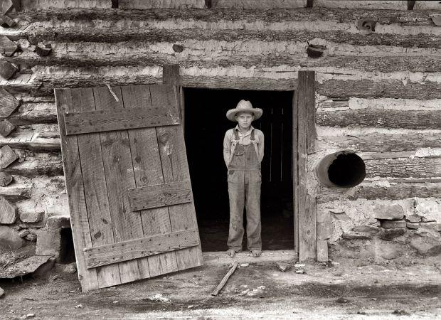 Farm Boy: 1939 Farm boy in the doorway of a tobacco barn, Person County, North Carolina.