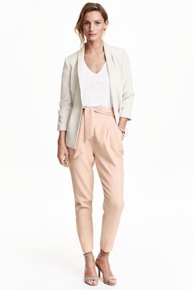 Плиссированные брюки: Свободные брюки из тканого материала. На брюках высокая талия с декоративными защипами спереди и пояс. Боковые карманы и прорезной задний карман. Потайная молния сбоку. Зауженные к низу брючины.