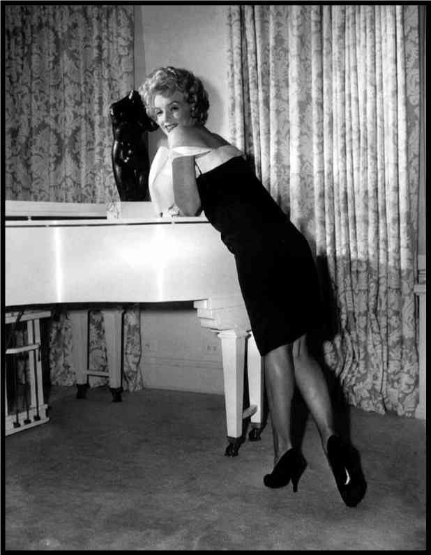 Marilyn Monroe and her white piano which Mariah Carey purchased and now owns.