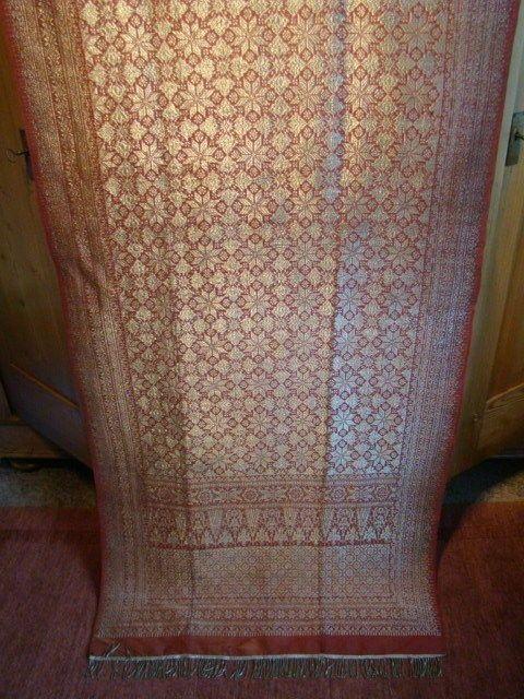 Kain Songket ceremoniële doek - Palembang - Sumatra - Indonesië  Mooie en in goede conditie verkerende Kain Songket. Ceremonieel heup- of schouderdoek afkomstig uit Sumatra / Palembang. Dit fraaie doek is uitgevoerd in warm-rode natuurzijde met zilverbrokaat en nog compleet met de bamboekoker waarin het ooit vervoerd is. Op foto 4 zijn drie uiterst kleine scheurtjes te zien. Het doek is in goede conditie en vrij van vlekken. De lichte lengtestrepen zichtbaar op de foto zijn vouwen overigens…