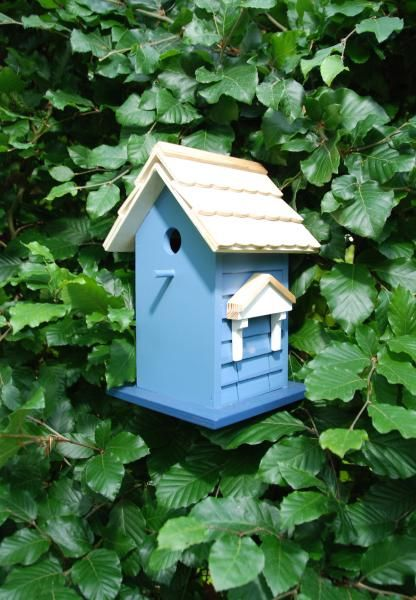 Fából készült, festett madárház négyféle színben.