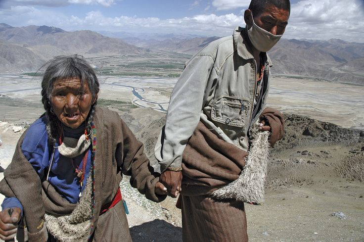 https://flic.kr/p/eEtoL | Tibetan pilgrims walking the Ganden kora | An old Tibetan women is led by her son while walking the kora at Ganden monastery. Kora is a religious exercise, in which a holy object is circumambulated - in this case the monastery itself and the adjecent hilltop. Ganden, appr. 50 km from Lhasa, lies at an altitude of 4800 m. During the cultural revolution it was virtually destroyed by Chinese artillery. Now it is being rebuilt. The young man told me this was the first…