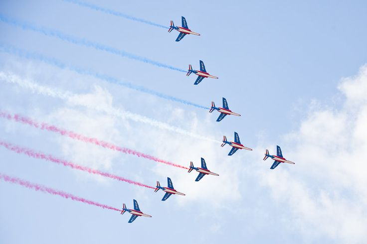 The blue, white and red smoke of the Patrouille de France illuminate the sky of Le Bourget at the 2015 Paris Air Show.