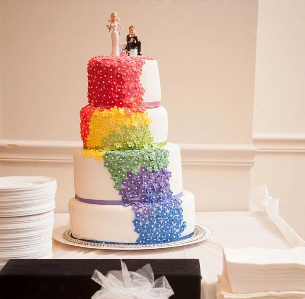 A cake with a cascading rainbow of flowers.