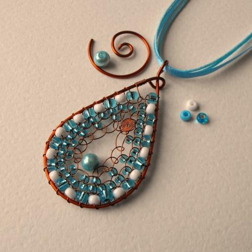 Zima Autorský drôtovaný šperk z medeného lakovaného drôtu a českých sklenených korálikov. Šperk je uchytený na tyrkysovo-belasej atlasovej šnúrke v kombinácii s dvomi bavlnenými šnúrkami. Zapínanie je na karabínku. Prívesok v tvare slzičky má rozmer 3,5cm x 6,5cm.
