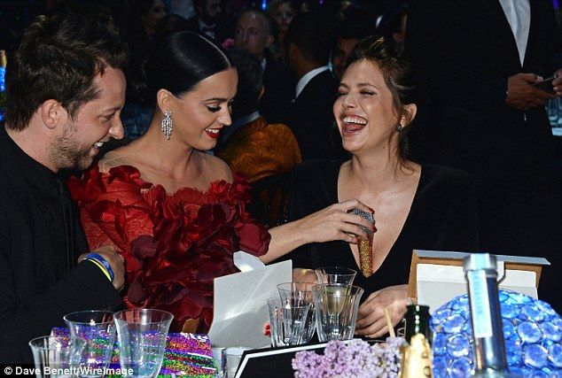 Cheeky! Katy puts her microphone down her friend Dasha Zhukova's top...