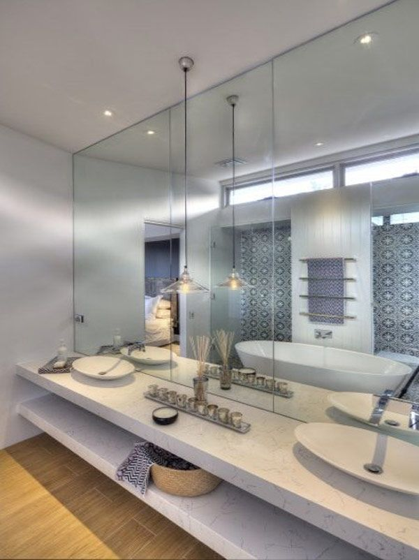 Great mirrored wall and double sink with all that shelving underneath.