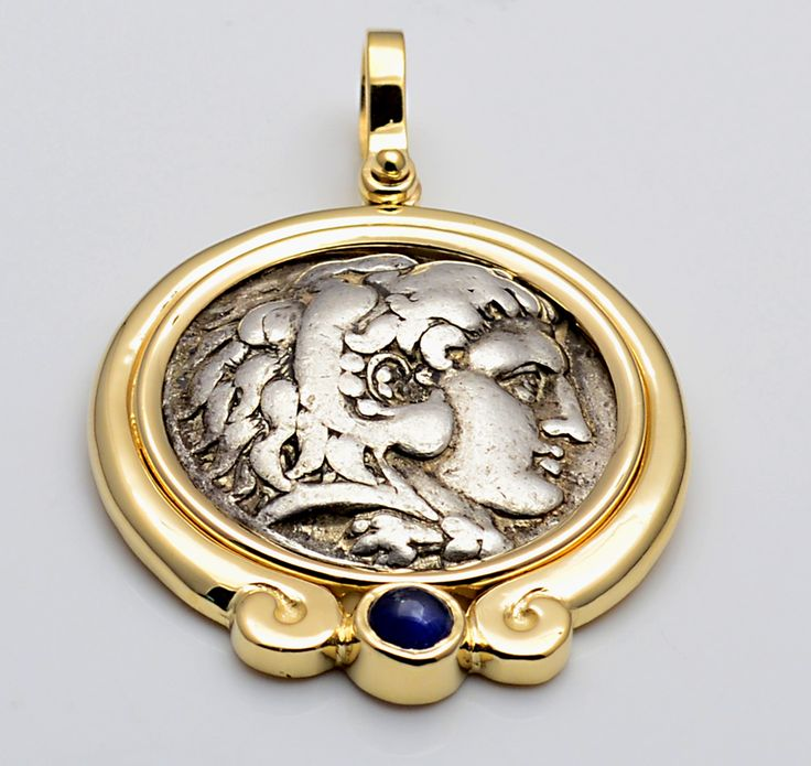 14kt gold and cabochon blue sapphire coin pendant with ancient Greek Macedon silver tetradrachm Alexander the Great. Circa 300 B.C. Available from Historicalcoin.com