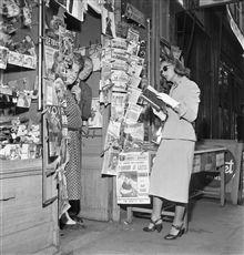 Irène Corday (1919-1996), actrice française, devant un kiosque à journaux. Paris, juin 1952.