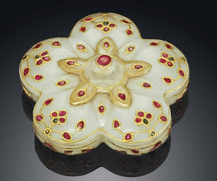 A MUGHAL-STYLE WHITE JADE INSET COMPARTMENTED BOX AND COVER  18TH/19TH CENTURY  The shallow box is of lobed floral form with the interior divided into six compartments. The cover is of a similar shape surmounted by a bud finial. Both sections are inset with semi-precious red and green stones within gold wire depicting flowers.
