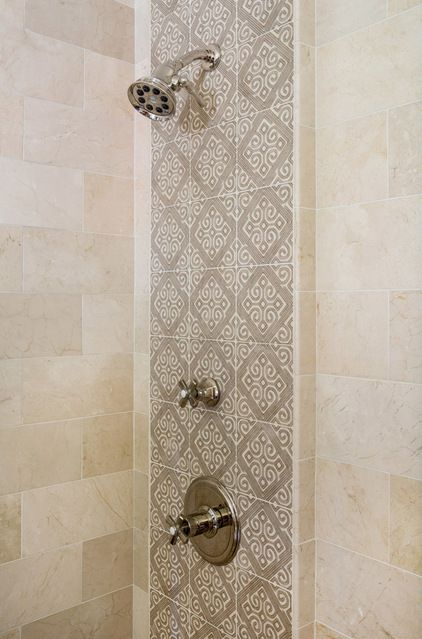 "Create a focal point with the shower plumbing wall. Because the shower fixtures were so pretty, Neithart wanted to showcase them and tie them together. She brought this section of wall 2 inches forward and covered it with accent tiles. ""If you create a landing strip for the plumbing, it makes it special,"" she explains."