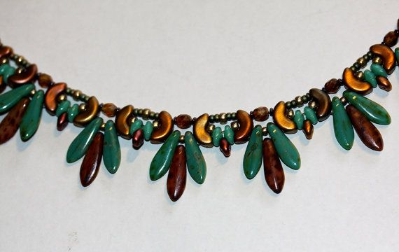 """My latest new design, a beadwoven necklace of Copper Toned Arcos Beads paired with Dagger beads in turquoise and warm brown, fire polished crystals, seed beads, and super duo beads. Original Amy Johnson Design. Nice light weight can be worn formal or everyday. Finished with a gold plated lobster clasp. Measures 18-1/2"""" to 20 long. Front measures 1 long. Packaged in my signature sage green box, carefully wrapped for safe delivery. View additional galleries at: http://www.amyj..."""