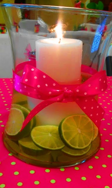 Limes submerged in a big glass container with ribbon that matches the wedding colors (or matches the table cloth?)