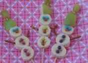 Sneeuwpop op een stokje  banaan met zoute sticks, hoedje van appel en druif met smarties o.i.d.