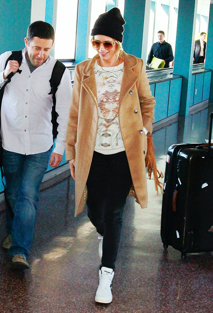 Kristen Wiig in a tan coat, black pants, and sneakers
