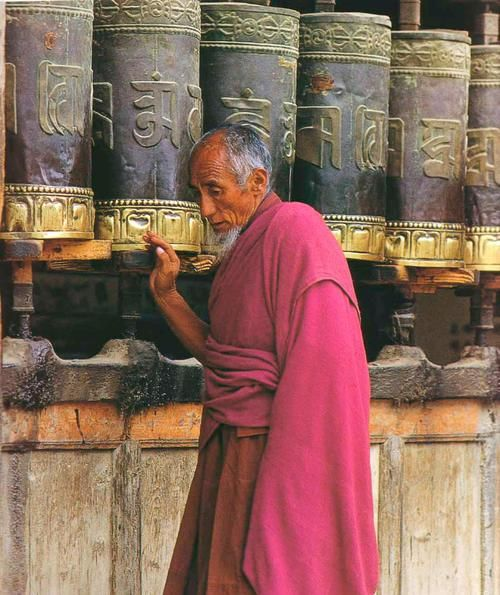 How to spin the beauty of prayers around the world. Buddhist monk turning prayer wheels in Tibet or Nepal.