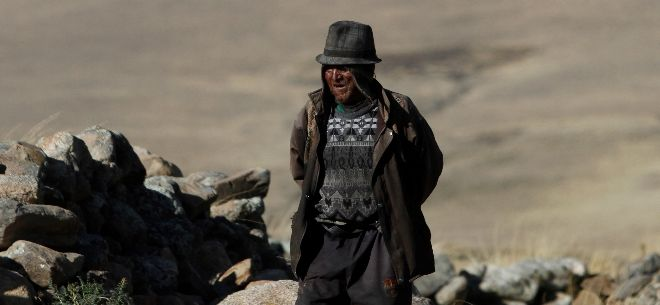 Carmelo Flores Laura, a native Aymara, stands near his home in the village of Frasquia, Bolivia on Aug. 13