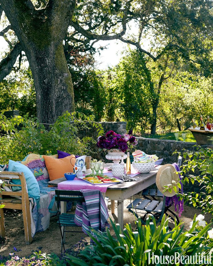 In a California house designed by Stephen Shubel, homeowner Gabriella Sarlo sometimes commandeers furniture from her cellar and sets it up outside for alfresco dining under century-old oak trees. The table, chairs, white bowls, and settee are from Chateau Sonoma. The rug over the settee is from Anthropologie, as are the glasses, purple bowl, and pitcher. The urn holding flowers is a French antique from stephenshubel.com.