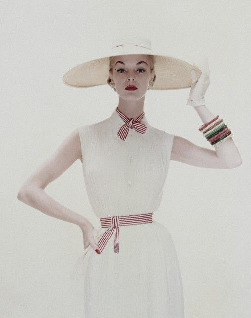 May 1954 Jean Patchett is wearing a white tucked crepe dress, of Dacron and rayon, tied with red and white stripes, by David Crystal; the hat, a wide circle of straw banded with white chiffon.