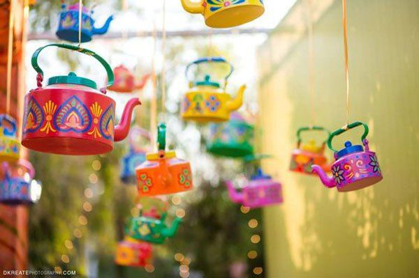 Indian Kitsch Mehndi Decor Ideas   Fun DIY Mehndi theme with super colourful Mehendi decor   Witty Vows   colourful kettles handing as decor with kitsch patterns