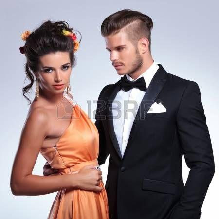 primo piano di una giovane coppia di moda con l'uomo che tiene la donna, mentre lei guarda la telecamera. su sfondo grigio