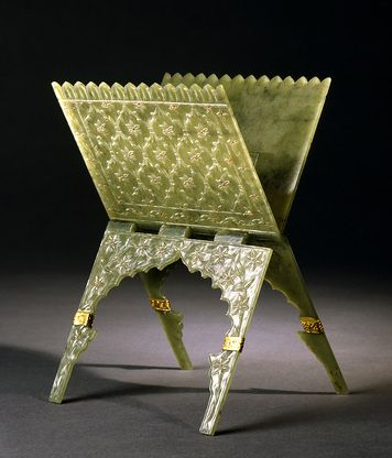 Koran stand, green jade, set with rubies India; c. 1700 H: 23.5; W: 14 cm This little Koran stand was masterfully executed in precious materials. It was carved from a single piece of jade that was split into two sheets, but carved so that the two parts are linked in the axis along which the stand opens. The outside of the stand is decorated with the vegetal ornamentation so typical of Mughal art, with flowers in a latticework at the top and delicate floral vines at the bottom that are set…
