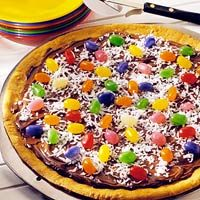 """Easter Cookie Pizza recipe: 1-20 oz roll refrigerated sugar cookie dough cut into ¼"""" slices. 1-16 oz can vanilla frosting. ¼ cup flaked coconut.1½ cups jelly beans."""