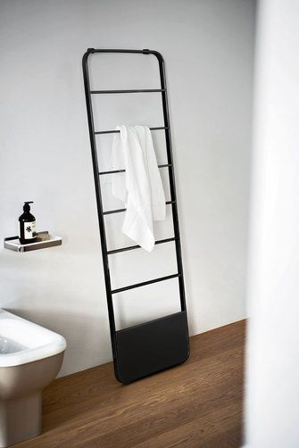An elegant and convenient selfregulating heated towel rail in steel with a polished chromeplated or black and white painted finish. It is attached to the wall through an invisible system.