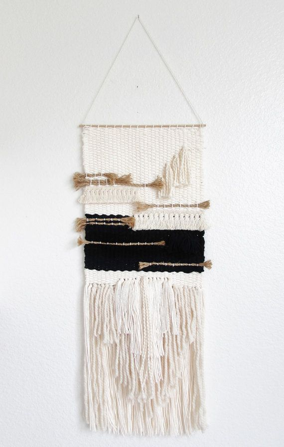 This stylish wall hanging is made by hand . Off white cotton and wool yarns, black cotton and a lot of texture bringing a beautiful chic and natural look. It hangs from a 12 wide wooden rod and is ready to hang. Due to the handmade process of this art form two weaves will never be exactly the same.     The weaving itself is long. It measures 12 by 30 for a total of 40 long from where it hangs to the bottom fringe Ships within 2-3 business days.   This item is delicate and made by hand by a…