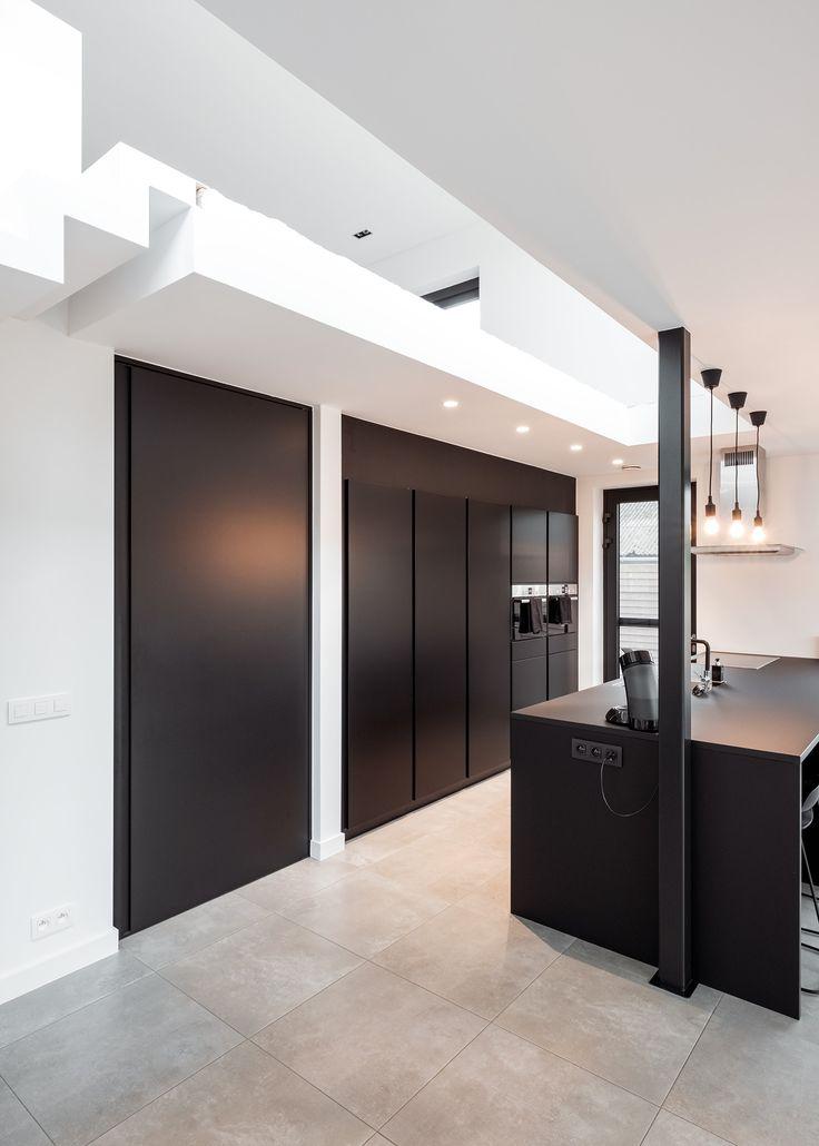 Zwarte binnendeur van vloer tot plafond in combinatie met een zwarte keuken van Kvik