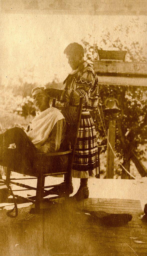 Unidentified Seminole barber at work in Estero, Florida. 1930