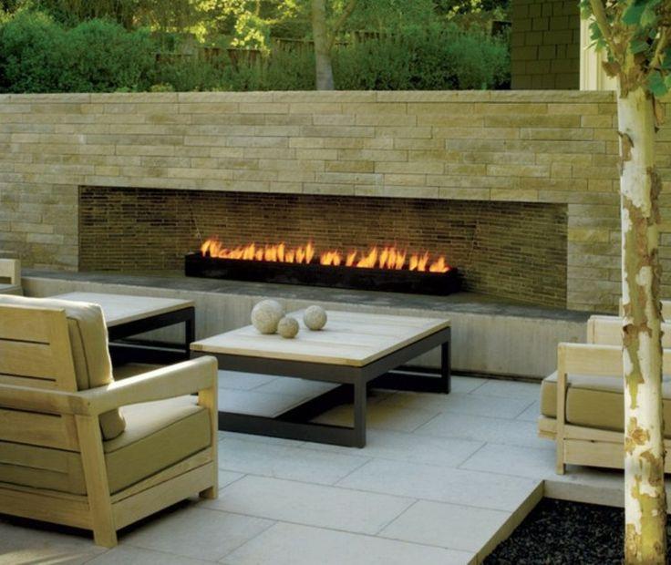 cheminée en pierre moderne sur la terrasse carrelée avec mobilier en bois