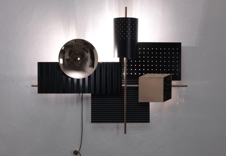 Luci oro e nere. In primo piano la lampada da parete Wallie by Lorenzo Bozzoli per il brand Tato