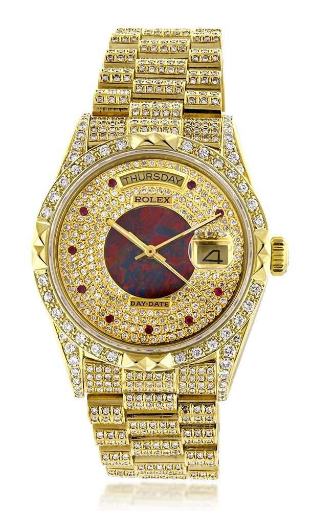This lavish Mens Rolex Oyster Perpetual Day-Date Custom Diamond Watch is made of solid 18K yellow gold and showcases 14 carats of custom after market set diamonds. Featuring a fully iced out look, this unique Rolex watch has an exquisite custom dial encrusted with diamonds, rubies and opal. This Rolex watch is secured with an 18K rose gold hidden fold clasp and is conveniently water resistant to 30 m (100ft)