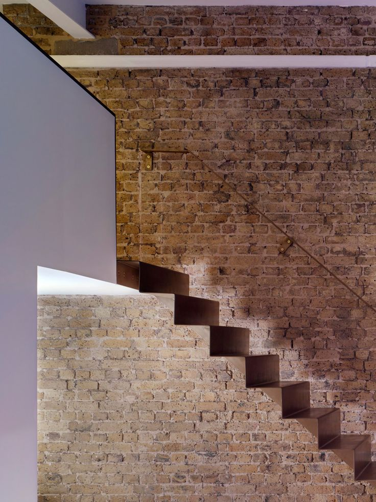 A folded steel staircase runs alongside an exposed brick wall to connect the two levels of this east London flat