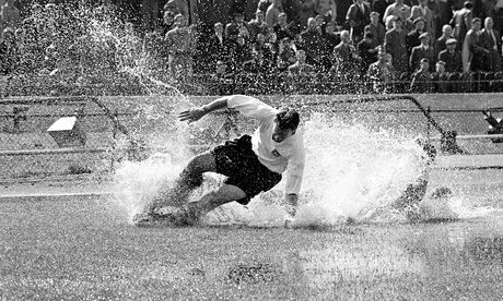 Preston North End's Tom Finney splashes through a puddle on 25 August 1956. Photograph: John Horton/PA