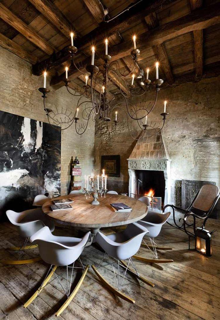 un lustre en fer forgé et une table en bois ronde dans le salon rustique